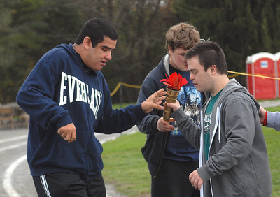 Upper Dauphin students L.J. Reyes and Daniel Schluben hand off the torch to Line Mountain student Lucas Hoffman during the running of the torch at the Area M Special Olympics at Line Mountain High School on Wednesday morning.