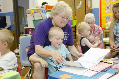 Ginnie Moore looks over a book that her grandson, Mason Cohoon, 5, helped to create with his kindergarten classmates at Watsontown Elementary on Thursday for their Authors Tea day.