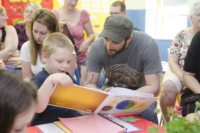 Ian Sanner, 6, left, shows his father Aaron Sanner a book which he helped to make during this kindergarten classes Authors Tea day at Watsontown Elementary on Thursday.