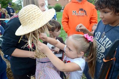 Abigail Harris, 4, Milton, helps pain the face of a scarecrow on Monday at a Milton Harvest Fest activity.