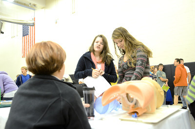 Evangelical Hospital paramedic Kathy Kling, left, talks with Milton 9th grade students Taylor Yarger, 14, and Carlena Russell, 14, during a career fair on Wednesday at the Milton High School.