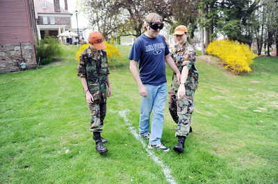Duane Rowe, of Mifflinburg, is guided by Lance Sampsell, 12 of Mifflinburg, and William Lapetina, 14 of Selinsgrove, while wearing drunk goggles at the Cherry Blossom Festival and Touch a Truck event at the Milton Public LIbrary at Rose Hill on Saturday morning. Samspell and Lapetina are cadets in the Civil Air Patrol Unit #522 out of Selinsgrove.