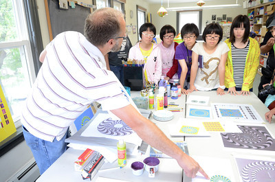 Sunbury YMCA Arts Center Creative Director Scott Onsager, left, shows a group of students from the Guangdong Experimental High School in China, projects that students have been working on, during a Monday tour of the center.
