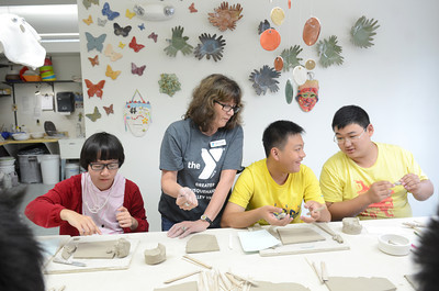Students from the Guangdong Experimental high School in China, Diaoyong Yin, 15, left, and Howie Lam, 16, and Peter Fu, 15, get some help from the Sunbury YMCA Arts Program Director Mary Jo Tavares, while making a pottery piece on Monday afternoon.