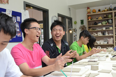 Jerry Mi, 16, left, and his classmate Rex Yang, 16, students at the Guangdong Experimental High School in China, share a laugh while working on pottery piece at the Sunbury YMCA Arts Center on Monday afternoon.
