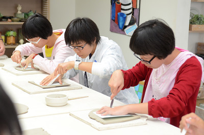Chinese students from the Guangdong Experimental High School, Diaoyong Huan, 15, left, Charlotte Zhang, 16, and Diaoyong Yin, 15, work on a pottery piece at the Sunbury YMCA Arts Center on Monday where they were visiting.
