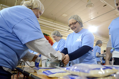 Millie Hockenbrock, left, and Kris Young, right, seal up bags of meals for the Kids Against Hunger program on Friday morning at the ConAgra plant in Milton.