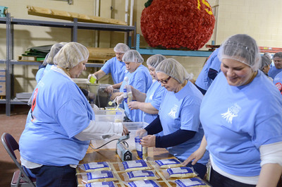 Current and former ConAgra employees fill up bags with food to help the Kids Against Hunger program on Friday morning.