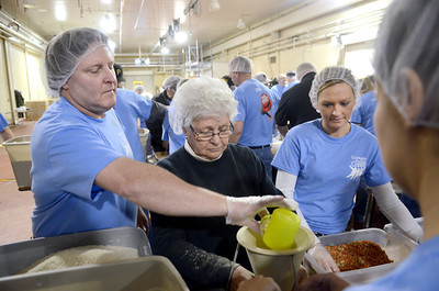 Current ConAgra employees Paul Rearick, left, and Heather Shuey, right, along with former employee Mary Kennedy, help pack up meals for the Kids Against Hunger program on Friday morning at the ConAgra plant in Milton.