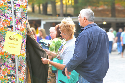 Wilma Wolfe, left, and Richard Smiley, of Kunkletown, check out quilts for sale at the Covered Bridge Festival on Thursday at Knoebels.
