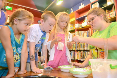 Carly Harter, 6, left, Keegan Gill, 9, and Laurel Ramsey, 6, get their materials from Rebeka Yocum at the Fizz Boom Reading activity on Monday at the Priestly Library in Northumberland.