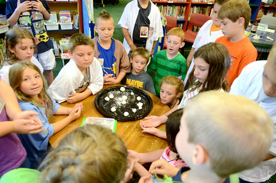 Kids at the Fizz Boom reading program get instructions on their project Monday afternoon at the Priestly Library in Northumberland.
