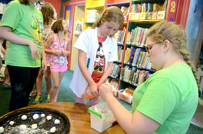 Sekota Golder, 9, sprays water into a powder held by Rebeka Yocum, 17, at the Fizz Boom reading program Monday afternoon at the Priestly Library.