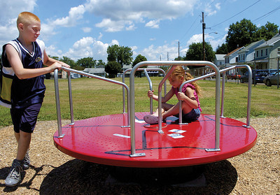William Spigelmeyer, 10 Sunbury, pushes his sister Chelsea, 4 Sunbury, on one of the new pieces of equipment at the Good Will Hose Company playground on Saturday.