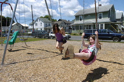Shyanne Kipple, 9 Sunbury, and Katy Johnson, 9 Sunbury, swing on the swingset at the Good WIll Hose Compnay playground during the grand opening on Saturday.