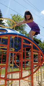 Shyanne, 9 Sunbury, climbs down a new piece of playground equipment during Saturday's grand opening of the Good WIll Hose Compnay playgroudn.