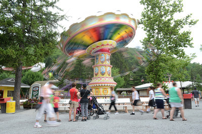 A ride whirls around at Knoebels as patrons walk past on Tuesday morning at the park.