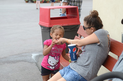 Asia Odenat, 3, left, gets a french fry from Natalie Edwards, Arizona, on Tuesday at Knoebels in Elysburg.