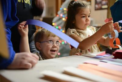 Holden Hammond, 2, and Savannah Hart, 5, both of Milton, make paper garland.
