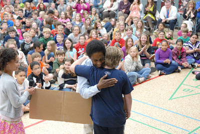 Milton Elementary 4th grade students Crystal Hamilton, left, and Ethan Rowe, get hugs from Special Olympian Loretta Claiborne Tuesday morning after presenting her with a check for the Special Olympics with money that the elementary school students raised.