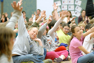 Milton Elementary School students raise their hands in answer to a question asked to them by Special Olympian Loretta Claiborne on Tuesday morning.