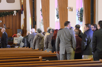 Friends and family of Merle Phillips wait in line at his viewing on Saturday before his funeral.