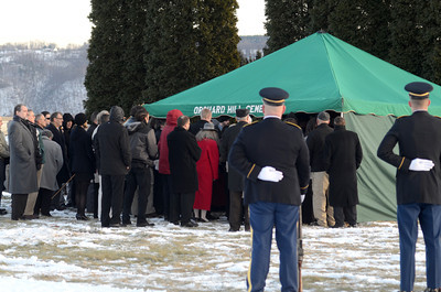 Mourners gather around the burial site of Merle Phillips on Saturday afternoon.
