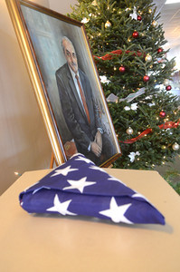 A flag that was placed with the coffin of Merle Phillips sits in front of a portrait of him painted by Tina Reiley, at his funeral service on Saturday.