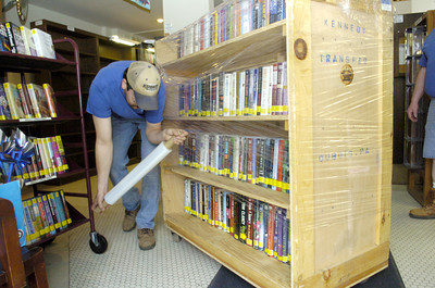 Roger Manning uses cling wrap to keep books in place on their carts to be moved from the old Milton Library location on Front Street to the new Broadway Street location on Monday.