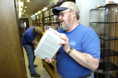 George Kramer of Kennedy Transfer loads up a cart full of books from the Milton Library's Front Street location on Monday in order to move them to the new Broadway Street location.