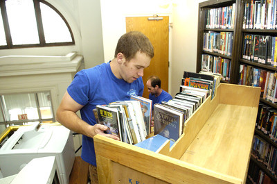 Zack Kennedy, left, and Shawn Yeager, of Kennedy Transfer, work together in packing up books from the Milton Library Front Street location to be moved to the Broadway Street location on Monday.