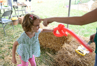 Pearl Allen, 5, of Watsontown duels with her mother, Bree, after picking up her balloon sword at the Northumberland Country Fair in Sunbury Friday Aug. 24, 2012.
