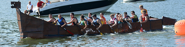 "Rowers on the cardboard boat ""Nessie"" work together to cross the finish line first in there heat during the regatta along the Susquehanna River Saturday Aug. 18, 2012 during the Sunbury River Festival."