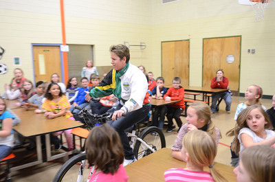 Montandon Elementary kindergarten teacher Jacqueline Martin, a two time olympic athlete in cycling, rides her bike into the school's Olympic assembly on Friday afternoon.