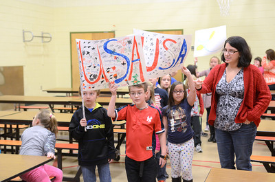 Montandon Elementary second grade students Dominic Ballo, left, Noah Haines and Alysa Paige-Miller, carry in banners their classes made to kick off the school's Olympic reading challenge on Friday.