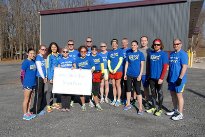 One Run For Boston leg 291 members Sonya Crane, left, Tina Bartholomew, Beatrice Benedit, Bethany Treas, Nathan Fisher, Kathy Pride, Ed Hoffman, Nancy Lee Harmon, Regina Hoffman, Carmella DiPippa, Bob Welby, Amanda Yagel, Bryan Yagel, Jason Deivert, and Doug Alter, pose for a photo before their leg of the run on Thursday in Stonington along Route 61.