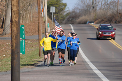 Mark Sullivan, left, takes the flag from Jeremy Hand and Caryn Hand as they finish up their leg of the One Run For Boston on Thursday morning at the Stonington Fire Company on Route 61.