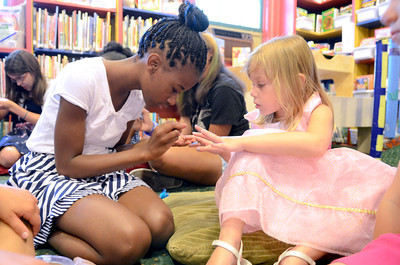 Kashmir Samuel, 12, left, paints the nails of Aubrie Garringer, 4, during princess day at the Priestly Library in Northumberland on Friday.