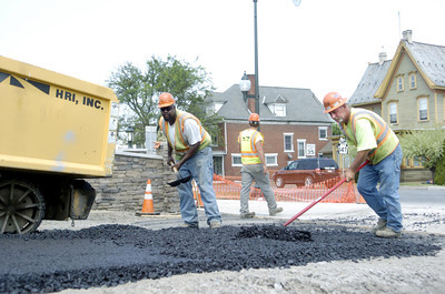 Lamar Brown and Don Taylor help to even out a patch of asphalt they were helping to complete on the River Front project in Sunbury on a hot Thursday afternoon.