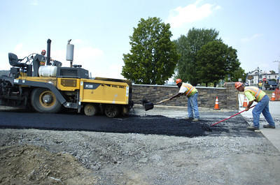 Workers Andy Zinck, left, Lamar Brown, and Don Taylor, lay asphalt on a access ramp along Front Street in Sunbury as part of the River Front project on a hot Thursday afternoon.