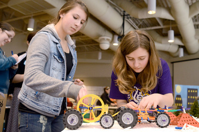 Southern Columbia 8th grade students Emily Wolfe, 13, left, and Casey Winter, 13, work on their teams Knex zombie snow plow vehicle at a STEM competition on Monday at the CSIU in Milton.