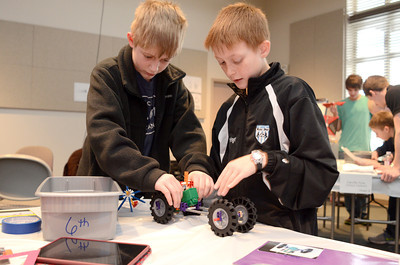 Midd-West 6th grade students Aidan Steininger, 12, left, and Morgan Stauffer, 11, help assemble their teams Knex car during a STEM competition on Monday at the CSIU in Milton.
