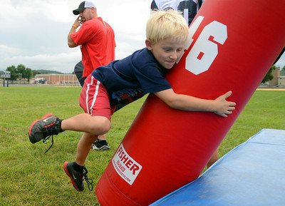 Arthur Skoff, 8, of Sunbury tackles a dummy during the Shikellamy Football Skills Camp Friday July 27, 2012 at the high school practice field.