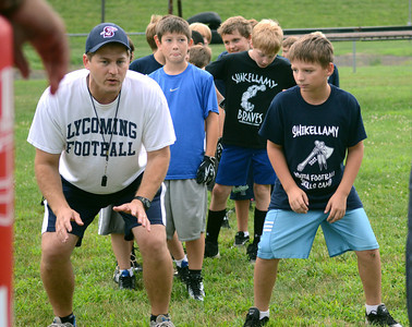 Coach Eric Shoch instructs Adam Young, 9, of Sunbury and other players during the Shikellamy Youth Football Skills camp Friday July 27, 2012.