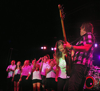 Amanda August/For The Daily Item A member of the Shikellamy High School Choir is pulled to the front of the stage by Foreigner member Jeff Pilson during their concert at Spyglass Ridge Winery on Saturday night.