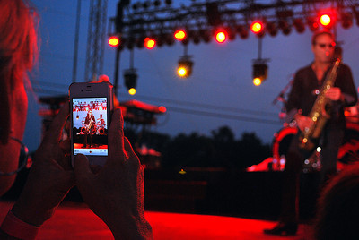 Amanda August/For The Daily Item A fan takes a photo of Foreigner during the concert at Spyglass Ridge Winery on June 29, 2012.