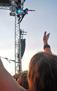 Amanda August/For The Daily Item A fan yells towards Kelly Hansen, lead vocalist of Foreigner, as he hangs from the top of the stage during the concert at Spyglass Ridge Winery outside of Sunbury on Saturday night.