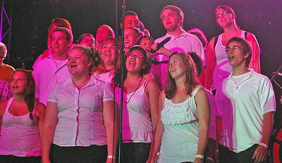 Amanda August/For The Daily Item Members of the Shikellamy High School Choir sing on stage with Foreigner on Saturday night at Spyglass Ridge Winery.