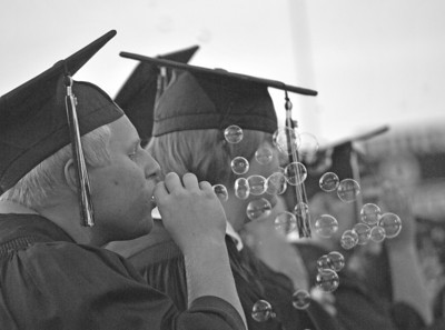 Amanda August/For The Daily Item Shikellamy graduate Cody Welsh blows bubbles during the Shikellamy High School commencement ceremony on Friday night in Sunbury.