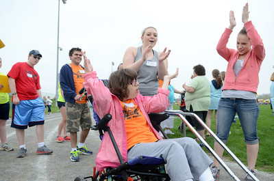 Milton student Emily Wertz, left, celebrates with Milton teaching assistant Monica Baker and health aide Jen Knobloch while bowling at a field day for special education students at the Warrior Run High School football field.